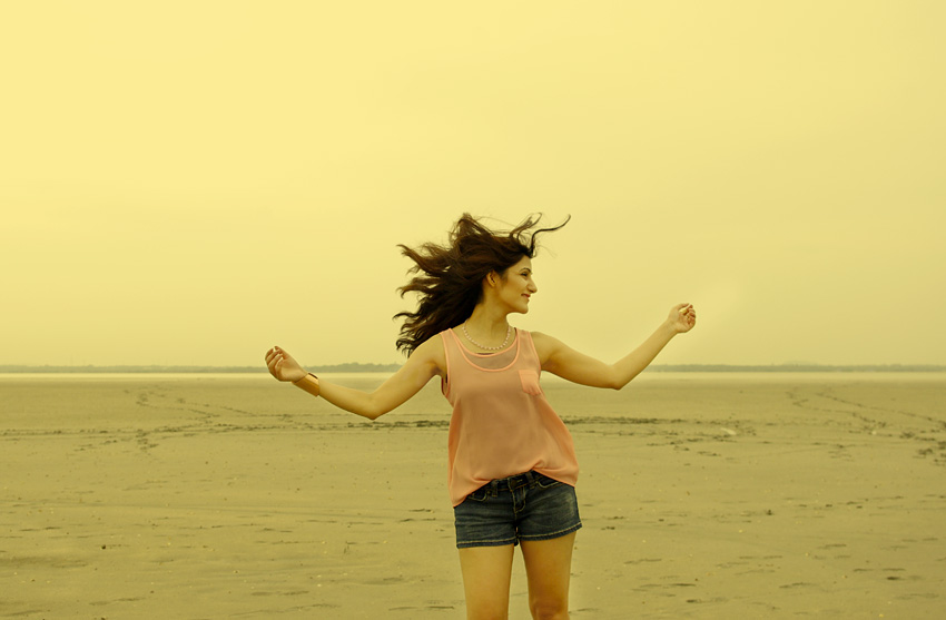 travel-girl-happy-traveling-beach-wind-blowing-hair